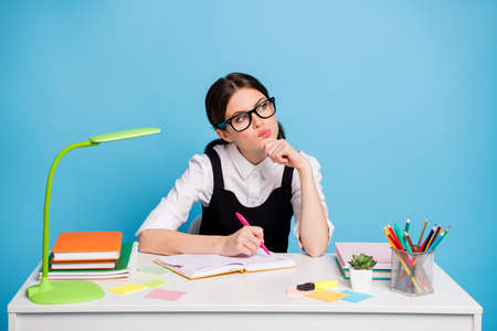 Photo pensive smart girl sit table write copybook exam graduate preparation look copyspace touch hand chin wear white blouse stylish trendy uniform black overall isolated blue color background 免版税图像