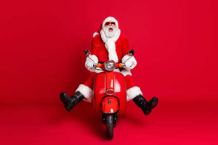 Full length photo of retired grandfather white beard mad ride retro moped open mouth spread legs fast ride down hill wear x-mas costume coat sunglass cap isolated red color background