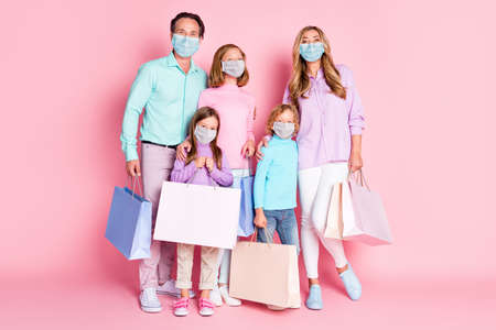 Full size photo of big full family mom dad little kids hold bags wear respiratory isolated over pastel color background