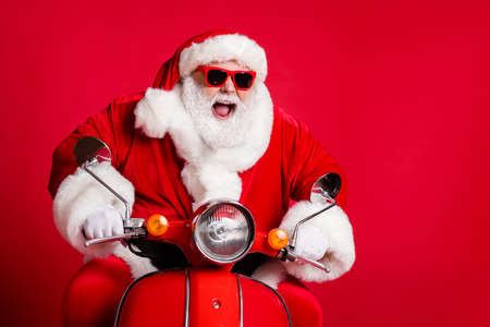 Photo of retired grandfather white beard ride retro scooter open mouth mad careless overtake slow cars fast have fun wear x-mas costume coat sunglass cap isolated red color background
