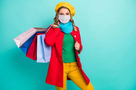 Phoro of positive cheerful girl hold bags wear mask green blue scarf headwear isolated over turquoise color background 版權商用圖片