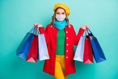 Photo of positive cheerful girl hold many bags wear mask red blue yellow sweater trousers isolated over turquoise color background