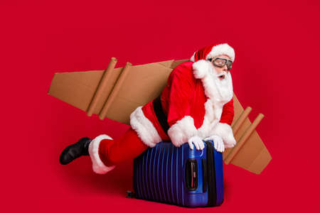 Full body size photo of retired infantile grandpa white beard ride suitcase jetpack almost fallen from sky wear santa x-mas costume coat spectacles headwear isolated red color background
