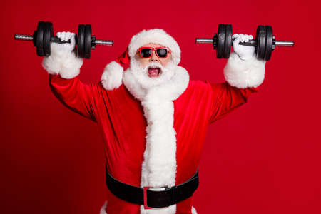 Photo of pensioner old man white beard lift heavy dumbbells smiling open mouth screaming get mad excited training wear santa costume sunglass headwear isolated red color background