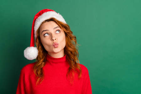 Photo of funny charming lady look up empty space pout lips wear red pullover x-mas cap isolated green color background 免版税图像
