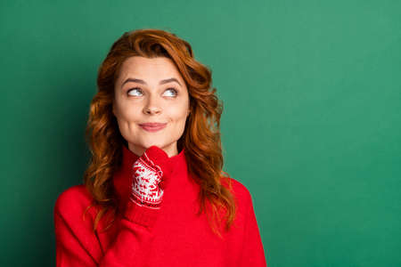 Photo of minded interested pretty girl finger chin look empty space wear red pullover mittens isolated green color background