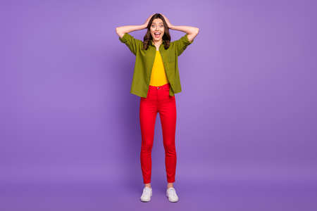 Full size photo of astonished girl have free time trip see wonderful bargain impressed scream touch hands head wear casual style clothes sneakers isolated purple color background