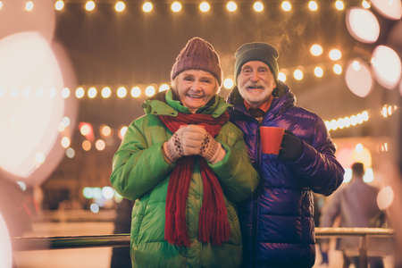Photo of two people pensioner couple promenade hold cups drink hot chocolate smoke fly from mug wear mittens coat red scarf headwear x-mas night street park shiny lights fair outdoors