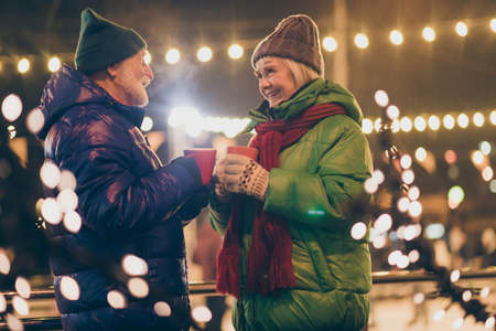 Photo of two people pensioner couple hold mugs drink eggnog comfortable cheerful smile newyear atmosphere wear mittens coat red scarf headwear x-mas night street park lights fair outside