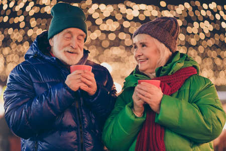 Two grey white hair old people parents married couple enjoy x-mas christmas spirit walk date under evening illumination outside hold aromatic beverage mug