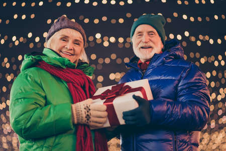Grey white hair two people old parents married couple woman man enjoy x-mas christmas atmosphere walk hold give big dream gift box under outside evening illumination