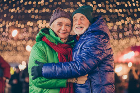 Photo of dream two people old man woman couple enjoy x-mas christmas advent eve time date hug embrace under evening illumination outside 免版税图像
