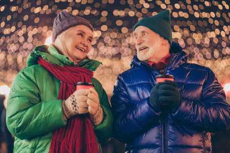 Photo of affectionate dream two old people married couple enjoy look x-mas christmas advent walk hold takeaway beverage mug under illumination outside wear coat scarf headwear 免版税图像