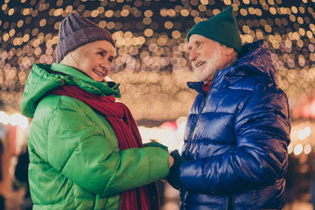 Back young ages. Adorable two people retired pensioner woman man have x-mas christmas newyear date under noel center illumination hold hand wear season coat headwear
