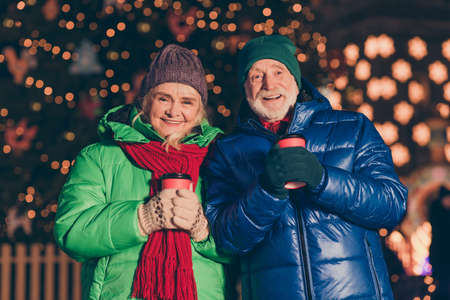 Two old people woman man have x-mas christmas jolly time night walk hold hot warm takeout beverage mug in city center outside under illumination wear season outerwear scarf hat