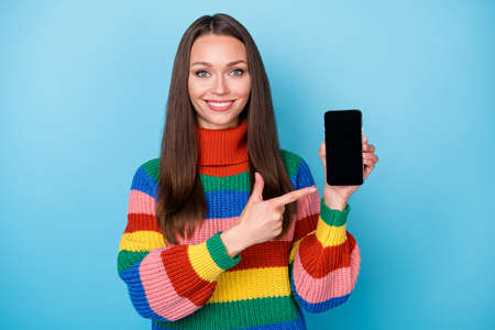 Portrait of her she attractive lovely cheerful girl holding in hand demonstrating gadget service screen new novelty product isolated bright vivid shine vibrant blue color background 版權商用圖片