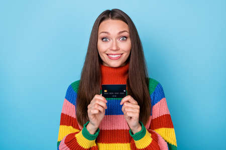 Portrait of positive cheerfull girl hold credit card recommend pay purchases online wear rainbow style jumper isolated over blue color background Stockfoto