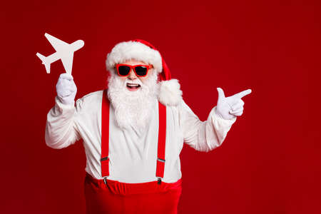 Portrait of his he attractive cheerful glad fat Santa holding in hands paper plane showing advice ad advert copy space isolated bright vivid shine vibrant red burgundy maroon color background 免版税图像