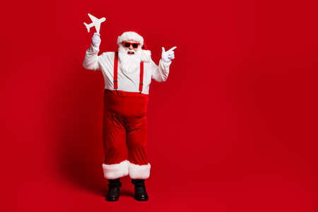 Full length body size view of his he attractive cheerful cheery fat Santa holding in hands paper plane showing copy space isolated bright vivid shine vibrant red burgundy maroon color background