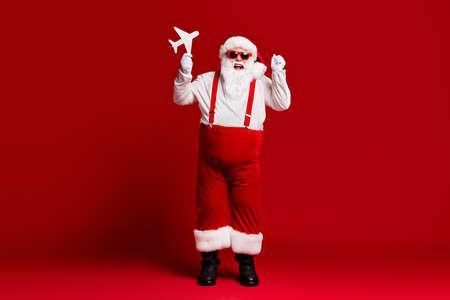 Full length body size view of his he attractive cheerful lucky glad fat Santa holding in hands paper plane having fun isolated bright vivid shine vibrant red burgundy maroon color background 版權商用圖片 - 157609171