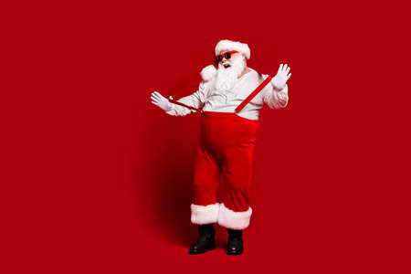 Full length body size view of his he attractive cheerful fat white-haired Santa having fun pulling suspenders fooling isolated bright vivid shine vibrant red burgundy maroon color background Stockfoto