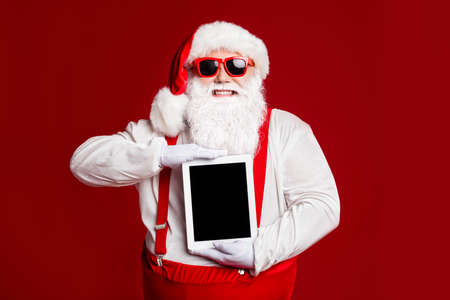 Portrait of his he attractive cheerful cheery fat white-haired Santa holding in hands demonstrating ebook isolated bright vivid shine vibrant red burgundy maroon color background 版權商用圖片