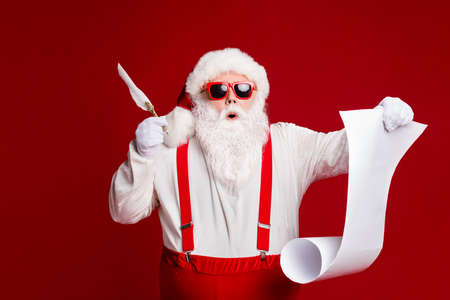 Portrait of his he attractive amazed stunned funny fat white-haired Santa writing wish present list North Pole isolated bright vivid shine vibrant red burgundy maroon color background