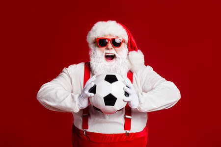 Portrait of his he attractive cheerful cheery glad fat white-haired Santa holding in hands throwing soccer ball hobby isolated bright vivid shine vibrant red burgundy maroon color background