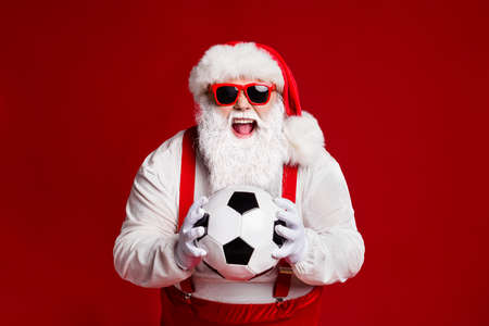 Portrait of his he attractive cheerful cheery ecstatic fat white-haired Santa holding in hands soccer ball having fun isolated bright vivid shine vibrant red burgundy maroon color background