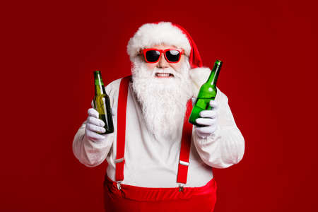 Portrait of his he attractive cheerful cheery funny fat white-haired Santa holding in hand beer bottles invite festal event isolated bright vivid shine vibrant red burgundy maroon color background