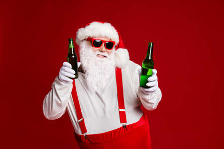 Portrait of his he attractive cheerful funny fat white-haired Santa holding in hand beer bottles dancing chill having fun isolated bright vivid shine vibrant red burgundy maroon color background