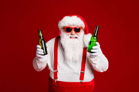 Portrait of his he attractive cheerful cheery funny fat white-haired Santa holding in hands beer bottles having fun isolated over bright vivid shine vibrant red burgundy maroon color background 版權商用圖片