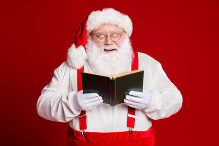 Portrait of his he attractive cheerful cheery funny amazed fat white-haired Santa reading interesting book isolated over bright vivid shine vibrant red burgundy maroon color background