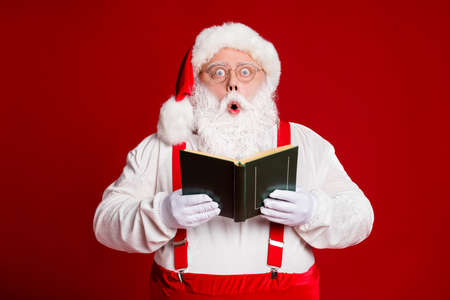 Portrait of his he attractive wise funny amazed fat white-haired Santa father reading book pout lips reaction omg isolated over bright vivid shine vibrant red burgundy maroon color background Archivio Fotografico