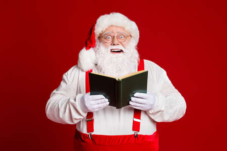 Portrait of his he attractive wise cheerful cheery fat white-haired Santa father reading interesting book having fun isolated over bright vivid shine vibrant red burgundy maroon color background