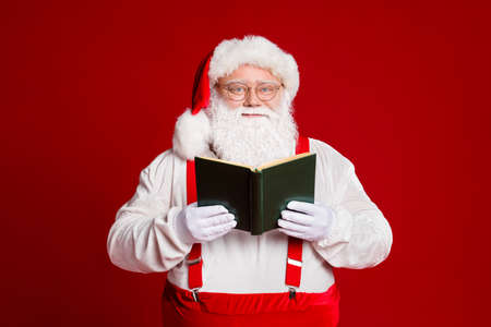 Portrait of his he attractive smart clever cheery white-haired Santa father reading fairy tale Eve Noel leisure isolated over bright vivid shine vibrant red burgundy maroon color background