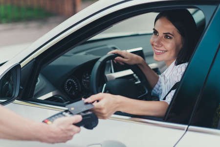 Close-up portrait of her she attractive cheerful content successful lady consumer riding car paying virtual money cash using pay pass buying goods product web connection transfer