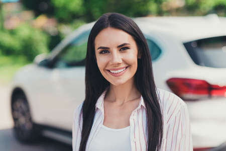 Close-up portrait of her she nice attractive pretty cheerful cheery lady lucky experienced driver new owner near white car credit debit loan buying vehicle motor summertime season Фото со стока