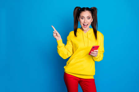 Portrait of nice attractive pretty lovely glad amazed cheerful cheery girl using device 5g app demonstrating copy space advert isolated over bright vivid shine vibrant blue color background