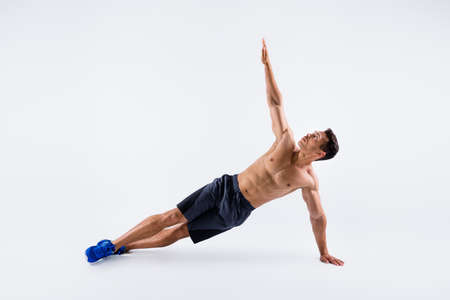 Full length photo of handsome macho sportsman dark skin guy chest warming up exercise focused stand plank on one arm body sculpt wear shorts sneakers isolated white color background