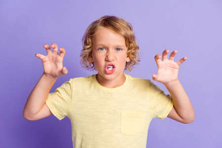 Photo of frightening small boy look in camera raise hands claws isolated over violet color background