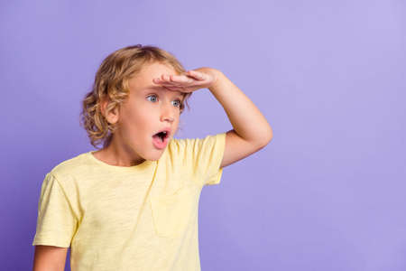 Photo of astonished boy look copyspace put hand near eyes face isolated over violet color background