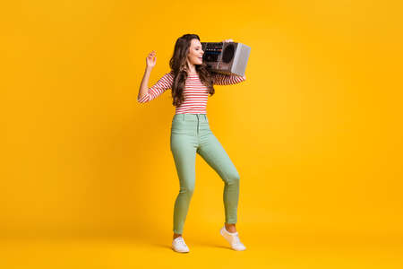 Full length body size photo of young girl listening music with retro boombox isolated on vivid yellow color background