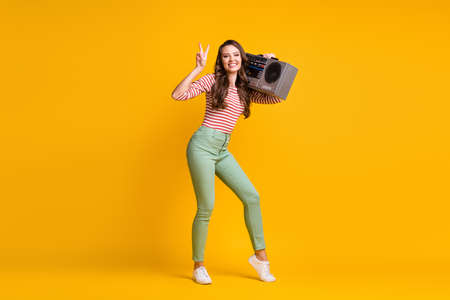 Full length body size photo of girl listening to retro boombox showing v-sign gesture isolated on vivid yellow color background 版權商用圖片