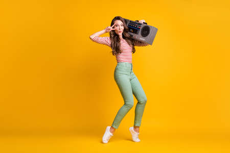 Full length body size photo of girl listening to retro boombox showing v-sign dancing isolated on bright yellow color background
