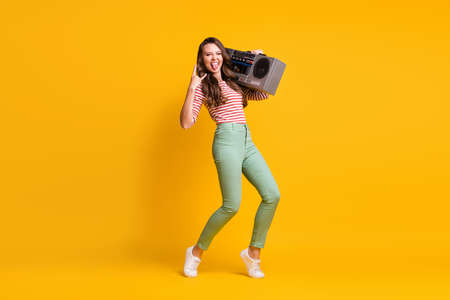 Full length body size photo of girl listening to retro boombox showing horns heavy metal sign isolated on vibrant yellow color background