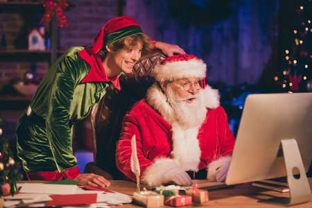 Photo portrait of santa claus and elf browsing internet on desktop Stockfoto