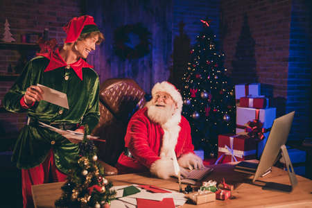 Photo portrait of santa claus and elf looking at each other holding paper mail Stockfoto