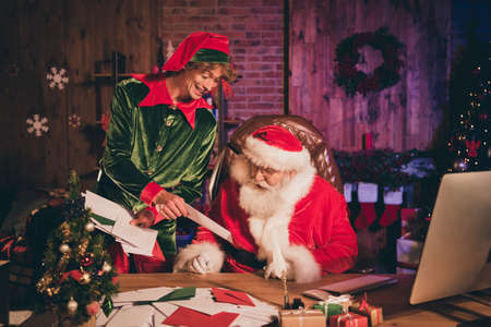 Photo portrait of elf showing santa claus paper letter