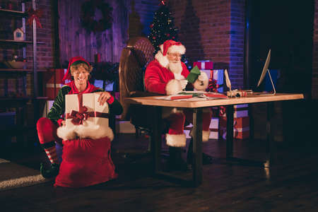Photo portrait of santa claus reading green letter from child and elf putting wrapped present into sack Stockfoto
